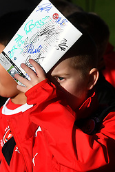 A young fan shields his face from the sun as he waits for autographs