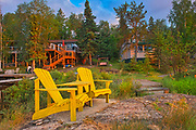 Cottages and Muskoka chairs  at Star Lake at sunrise. Cottage Country Living.<br />Whiteshell Provincial Park<br />Manitoba<br />Canada