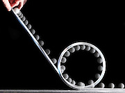 .This is a demonstration of a ball rolling down an incline and making the loop-the-loop path.  The velocity required to make the loop is called the critical velocity.   The analysis of this demo requires the use of the centripetal force, kinetic energy, potential energy, rolling energy, and friction.  This is also an example of a critical velocity.  The loop is 19.5 cm in diameter and the ball is 2.5 cm in diameter. The flash illuminates the scene at 40 hz showing images every  .025 seconds of time. .
