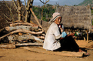 Burma/Myanmar. Elderly man sitting with a child near a house in the Akha village.