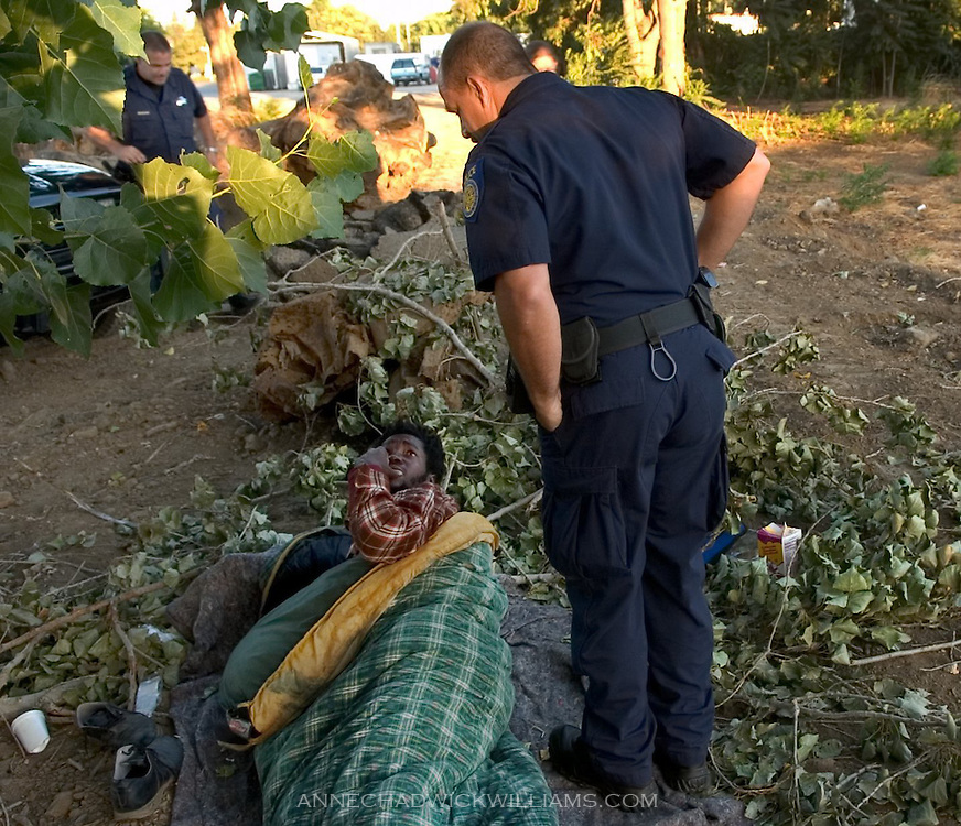 """Sacramento police officer Mike Cooper wakes up Maynard Philips who was sleeping in a field near the Union Gospel Mission in Sacramento, CA on August 4, 2005.  Cooper and Mark Zoulas, back left, acknowledge that their goal is """"to get everyone out of here,"""" but it takes longer with some people."""
