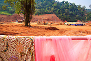14 MARCH 2013 - ALONG HIGHWAY 13, LAOS:  Laundry from a brothel hangs in front of a car park being paved to accommodate Chinese traffic at the end of Highway 13 in the Boten Special Economic Zone. The SEZ is in Laos immediately south of the Lao Chinese border. It has turned into a Chinese enclave but many of the businesses struggle because their goods are too expensive for local Lao to purchase. The Lao businesses on the site, salt evaporation factories, will have to relocate when the parking area is finished. Some of the hotels and casinos in the area have been forced to close by the Chinese government after reports of rigged games. The paving of Highway 13 from Vientiane to near the Chinese border has changed the way of life in rural Laos. Villagers near Luang Prabang used to have to take unreliable boats that took three hours round trip to get from the homes to the tourist center of Luang Prabang, now they take a 40 minute round trip bus ride. North of Luang Prabang, paving the highway has been an opportunity for China to use Laos as a transshipping point. Chinese merchandise now goes through Laos to Thailand where it's put on Thai trains and taken to the deep water port east of Bangkok. The Chinese have also expanded their economic empire into Laos. Chinese hotels and businesses are common in northern Laos and in some cities, like Oudomxay, are now up to 40% percent. As the roads are paved, more people move away from their traditional homes in the mountains of Laos and crowd the side of the road living off tourists' and truck drivers.    PHOTO BY JACK KURTZ