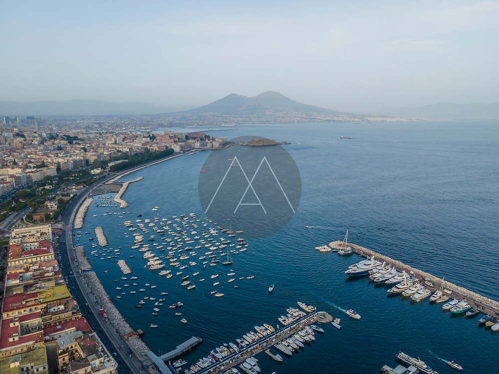 Panoramic aerial view of Naples downtown, view of the Vesuvius volcano over the city skyline facing the Mediterranean Sea, Campania, Italy.