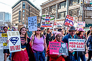 """San Francisco, USA. 19th January, 2019. At the Women's March San Francisco, marchers carry signs concerning Medicare for all, politcal corruption. A young woman wears a Super Girl costume and holds a sign: """"All girls are Super Girls."""" Credit: Shelly Rivoli/Alamy Live News"""