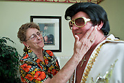 """Aug. 2 - PHOENIX, AZ: JANE TRAPANI pats her husband, DONALD TRAPANI, on the cheek after he finished dressing as Elvis Presly before he performed as the """"King"""" at the Stratford, an Alzheimer's care facility in Phoenix. Trapani, 68, was diagnosed with lung cancer in August 2009 and entered the care of Hospice of the Valley, the largest hospice organization in Phoenix, shortly after that. His doctor said he would be dead by the end of February 2010. Trapani is in still in the care of Hospice of the Valley, but his condition has improved. He now entertains other hospice patients singing the songs of Elvis Presley. He tries to hold one concert each week, his health permitting, at different hospice units in the Phoenix area.     Photo by Jack Kurtz"""