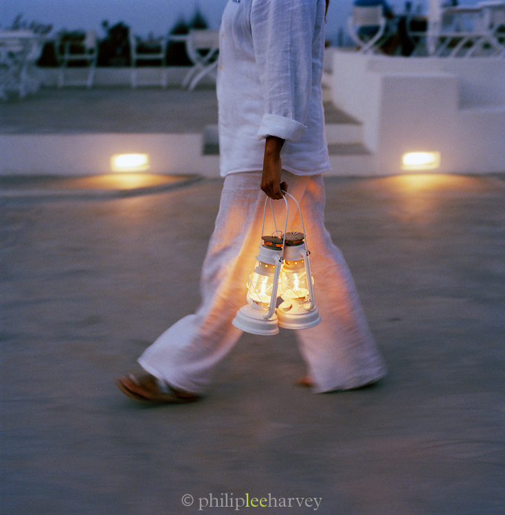 Staff carrying lamps at a hotel in the Aeolian Islands, Italy