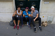 Teenagers watch the match between France and Croatia in the World Cup Final, on a street in Paris, France.