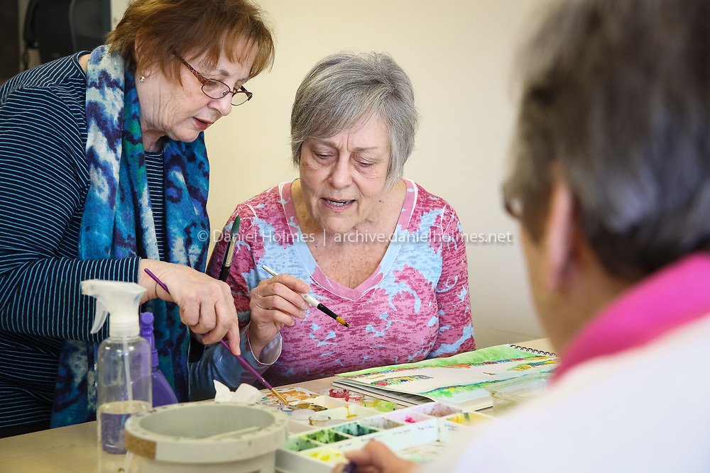 (3/25/15, MILFORD, MA) Instructor Carlie Nargi DeGaetano helps Cathy Johnson, of Franklin, with a painting during watercolor class at the Milford Senior Center on Wednesday. Daily News and Wicked Local Photo/Dan Holmes