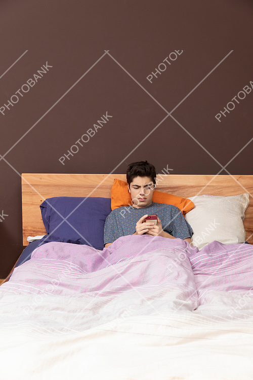 Boy in the bed with phone, he lose just time and maybe he chatting or he looks to something. Front position.