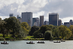 Beautiful day in Central Park overlooking the New York Skyline and people rowing boats in The Central Park lake