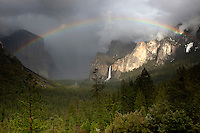 A beautiful rainbow appears over Yosemite Valley following a rain storm. El Capitan and the Bridal Veil Falls can be seen in the distance.