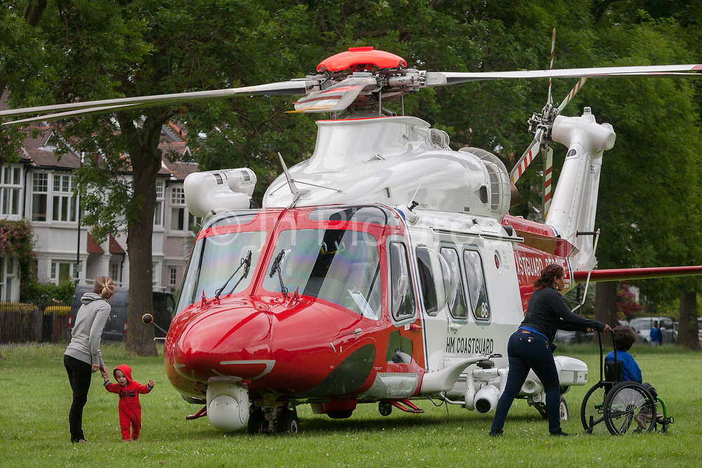 Local residents look closely at an AgustaWestland AW139 helicopter operated by the UK Coastguard rescue which is briefly landed in Ruskin Park to deliver an emergency patient, on 8th June 2017, in the south London borough of Lambeth, England. The AW139 is used by Her Majestys Coastguard HMCG which is a section of the Maritime and Coastguard Agency responsible for the initiation and co-ordination of all maritime search and rescue SAR within the UK Maritime Search and Rescue Region.