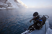 A diver prepares to go underwater, looking to catch King Crabs at a lake in Jarfjord, near Kirkeness, Finnmark region, northern Norway