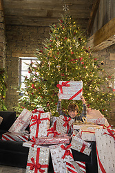 little boy holding up a package while surrounded by numerous Christmas packages by a large tree