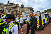 """Police arrested and searched an Animal and climate activist from Animal Rebellion outside Buckingham Palace, after they dyed blood-red Buckingham Palace fountains on Thursday, Aug 26, 2021 - signifying as their statement said """"its' demonstrable role in hunting and animal agriculture"""". (VX Photo/ Vudi Xhymshiti)"""