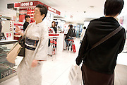 a middle aged traditional Japanese dressed woman walking through a luxury makeup retail store Tokyo Japan