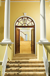 Front entrance of modern Florida Home with arched transom above from mahogany door and front columns