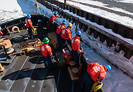 Crew members of the United States Coast Guard cutter Sturgeon Bay prepare to dock at a pier in Hudson, New York. The Sturgeon Bay was breaking ice in the shipping channel in the Hudson River.  Crew members wear personal flotation jackets, hard hats and eye protection while working on the deck.