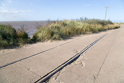 Road next to eroded railway line at Spurn Head; East Yorkshire; England; with Humber Estuary on the left,