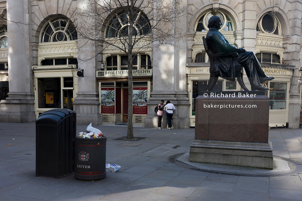 Statue of Sir George Peabody near overflowing litter bin and City of London urban Victorian landscape.