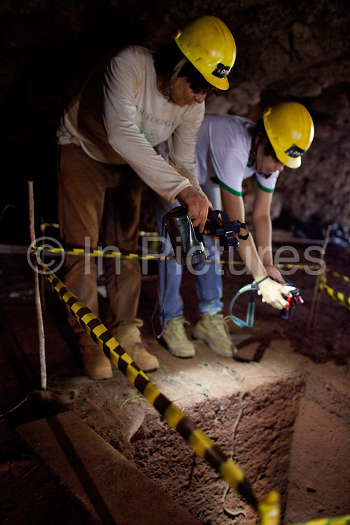 Archaeologists surveying a cave site in the Carajas national forest, an unique type of svaanna deep in the rainforest. The Carajas Open Cast Iron Ore mine is the largest iron mine in the World, estimates say the site can be mined at today's rates for another 400 years. In the Amazonian State of Para, Brazil, it is operated by the State owned Vale mining corporation, prevoously CVRD. The company has come under some controversy about the mine, and recently has started expanding the mine on the site of a series of ancient caves.