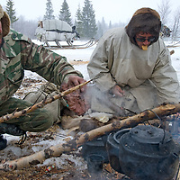 North of the Arctic Circle in Russia, nomadic Komi reindeer herders grill reindeer meat on a stick over coals of an outdoor campfire.