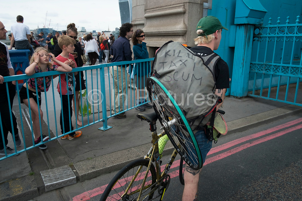 Cycle courier with kill taxt scum written on his couriers bag in London, England, United Kingdom. This slogan is most likely a protest at how cyclists are treated by car and other road users, including taxis. (photo by Mike Kemp/In Pictures via Getty Images)
