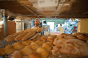 Jamestown, RI - 7 May 2007. Andrea Colognese of The Village Hearth Bakery and Cafe, putting loaves of bread fresh from the oven onto cooling racks.