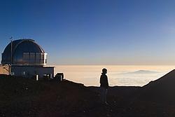 Woman visitor, United Kingdom Infrared Telescope or UKIRT, and Haleakala of Maui at distance, Mauna Kea Observatories, Big Island, Hawaii