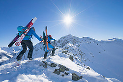 Rear view of skiers climbing on ridge of snow mountain