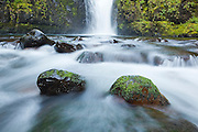 Low angle view of boulders and Sevenmile Falls, the uppermost major waterfall along Eagle Creek, Columbia River Gorge National Scenic Area, Oregon.