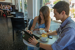 North America, United States, Washington, Kirkland, young couple with tablet pc in coffee shop.  PR, MR