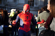 An entertainer dressed up as Spiderman makes obscene gestures in angry postures outside the National Gallery.  A large number of performers earn their money outside the national Gallery and the trade is good on a sunny day.