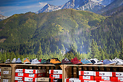 A display of shoes and their shoe boxes beneath a large photo of spruce forests and peaks of the nearby Tatra mountains, on 17th September 2019, in Zakopane, Malopolska, Poland.