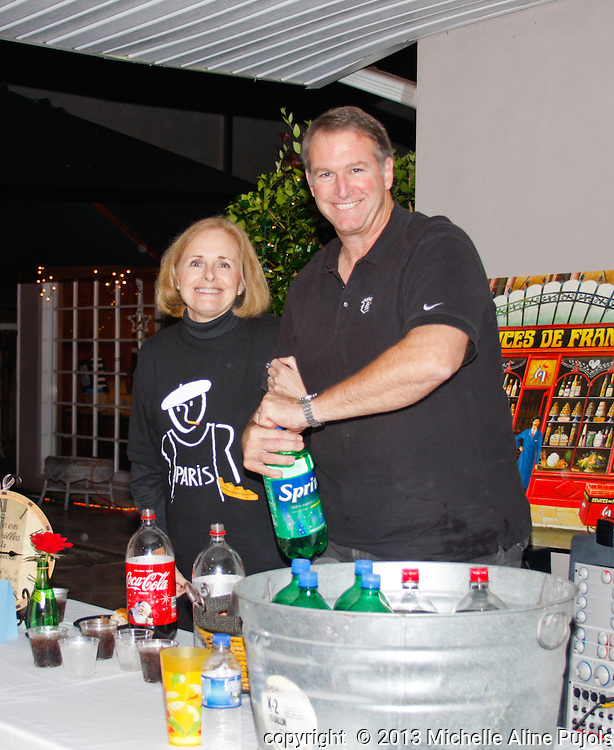 A couple serving a drink at a party.