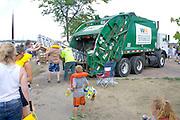 Volunteers stuff milk carton canoe into large truck for crushing and disposal. Aquatennial Beach Bash Minneapolis Minnesota USA