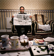 Murtza Rasul, 32, holds a newspaper article that allegedly shows his brother, Shafiq Rasul, with a bullet wound after he was captured in Afghanistan in 2001. Photographed at the family home in Tipton in the East Midlands, UK. Shafiq Rasul is being detained by the US at the Guantanamo Bay military base at the edge of Cuba. .