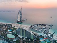 Aerial view of the luxurious Burj Al Arab Hotel and harbour at sunset on Dubai coast, U.A.E.