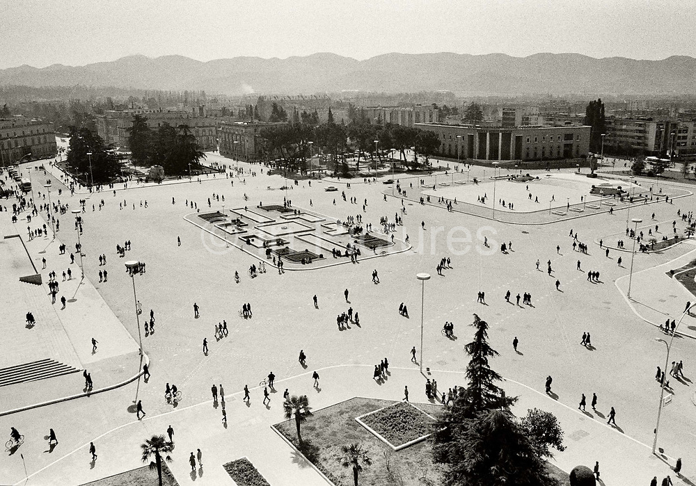 Skanderbeg Square, Tirana, rush hour 1pm. The quiet serenity of this busy scene is because prior to 1991, it was illegal to own a car in Albania. There were, of course, a few automobiles running around but these were either driven by high communist officials or municipal employees.<br /> <br /> In 1991 the Albanian government lifted the decades-old ban on private-vehicle ownership. Car imports numbered about 1,500 per month, and a black-market car lot began operating just behind the square. The number of cars in Albania has soared since the collapse of Communism, from 5,000 in the early Nineties, to over 500,000 today. Most are stolen from around Europe.<br /> <br /> The population has more than doubled since 1990 and is now well over 700,000, fuelled by an influx of migrants from rural areas. The city is now choked with some 300,000 cars, lorries and buses which burn fuel banned in the EU and Over 35,000 tons of exhaust gases are annually expelled in the capital alone, 10 times the WHO limit. Tirana is now the most polluted capital in Europe.