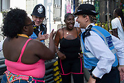 Party goers and two police officers laugh together at the Notting Hill Carnival, on 25th August, 2019 in London, United Kingdom. One million people are expected on the streets in scorching temperatures for the Notting Hill Carnival, Europes largest street party and a celebration of Caribbean traditions.