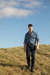 handsome man walking on a grassy hillside