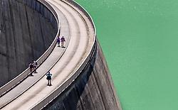 THEMENBILD - Hochgebirgsstauseen Kaprun. Sie dienen der Verbund AG zur Wasserspeicherung für die Stromerzeugung des Kraftwerks Kaprun und sind ein beliebtes Ausflugsziel fuer zahlreiche Touristen, die Mittels Busse und einem Schraegaufzug auf ueber 2000 Meter befoerdert werden. Der Spatenstich erfolgte 1939, ausgefuehrt von Hermann Goering. Seit 1999 gehoert es zur Verbund Hydro Power AG, dem Tochterunternehmen für Wasserkrafterzeugung der Verbund AG, im Bild Touristen gehen auf der Staumauer des Mooserboden Speichers. Bild aufgenommen am 27.07.2012. EXPA Pictures © 2012, PhotoCredit: EXPA/ Juergen Feichter