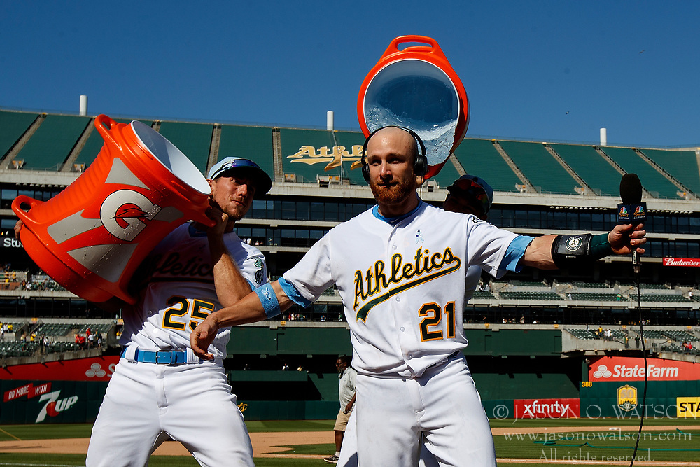 OAKLAND, CA - JUNE 17:  Stephen Piscotty #25 of the Oakland Athletics and Chad Pinder #18 pour water and Gatorade on Jonathan Lucroy #21 after he hit a walk off single against the Los Angeles Angels of Anaheim after the game at the Oakland Coliseum on June 17, 2018 in Oakland, California. The Oakland Athletics defeated the Los Angeles Angels of Anaheim 6-5 in 11 innings. (Photo by Jason O. Watson/Getty Images) *** Local Caption *** Stephen Piscotty; Chad Pinder; Jonathan Lucroy