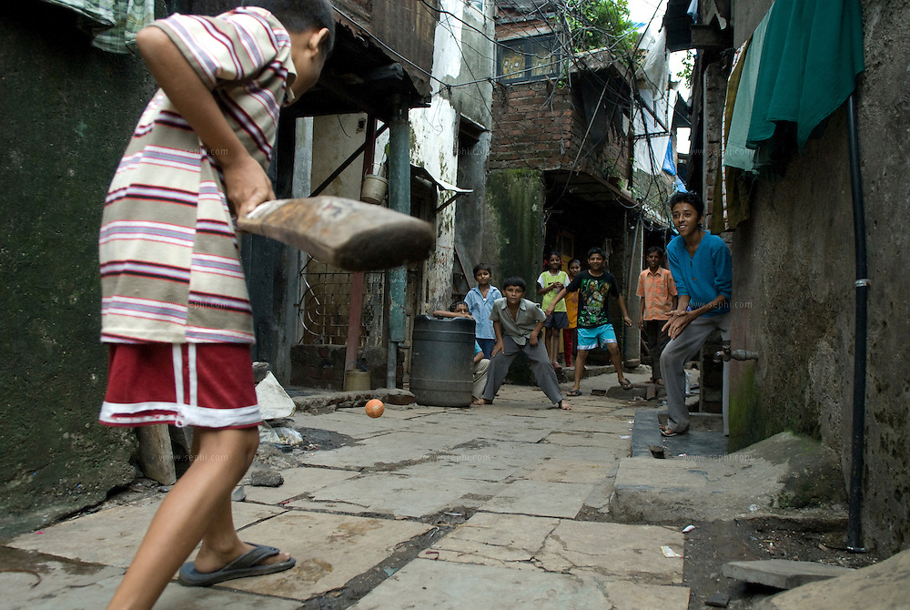 children play cricket in a crowded alley of dharavi slum. Mumbai, August 2007