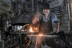 Blacksmith hammering hot iron bar on anvil at workshop, Bavaria, Germany