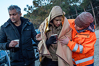 LESVOS, GREECE - FEBRUARY 09: A volunteer comforts a young Syrian man suffering from hypothermia after his arrival on a beach in South Lesvos with other refugees and migrants from the Turkish coast on February 09, 2015 in Lesvos, Greece. Photo: © Omar Havana. All Rights Are Reserved
