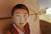 A young boy stares in disbelief at the camera, right in front of his yurt, in Western Mongolia, on the border with Russia.