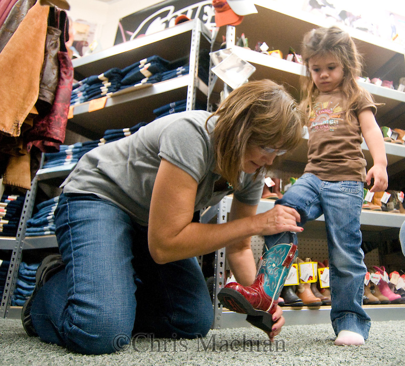 9/27/08 Valentine, NEB.Dandee Hepper, 4, gets tries on boots with Young's Western Wearhouse employee Lana Peterson.Dandee was with her mom Dacey Hepper...Chris Machian/for the New York Times