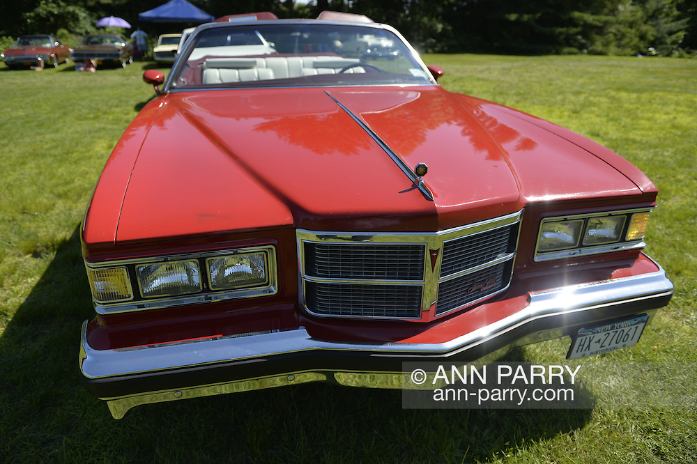 Old Westbury, New York, United States. 7th June 2015. A red 1975 Pontiac Grand Ville convertible, seen from front, is shown at the 50th Annual Spring Meet Car Show sponsored by Greater New York Region Antique Automobile Club of America. Over 1,000 antique, classic, and custom cars participated at the popular Long Island vintage car show held at historic Old Westbury Gardens.