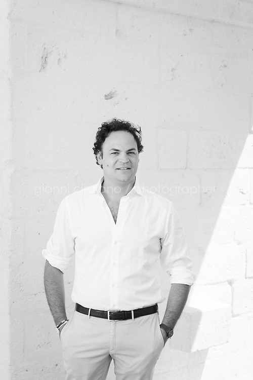 """FASANO, ITALY - 22 JULY 2018: Aldo Melpignano (40), proprietor of Borgo Egnazia, a high-end resort in Puglia, poses for a portrait here at Borgo Egnazia in Fasano, Italy, on July 22nd 2018.<br /> <br /> Borgo Egnazia, modeled after a 15th century Apulian village, rolls out over 250 acres on a plot of land originally razed by Mussolini and intended as an air force base, ending nearing the Adriatic. Aldo Melpignano, the 40 years old owner, has pioneered a hospitality company that has managed to seize on the hype surrounding wellness and authentic experiences at once. His company, SD Hotels, turns Puglia's traditional farmhouses into resorts that focus on fitness (Apulian folk dance classes in 400 year old olive groves) and otherworldly spa treatments (one massage uses """"vibrational water"""") in addition to traditional Italian fare (milk serum, handmade orecchiette pasta, octopus in a broth of just-plucked tomatoes). <br /> <br /> Borgo Egnazia is the largest of his five properties, with three public pools, a village square out of central casting, and nearly 200 rooms.  Celebrities like Madonna have been won over by Borgo Egnazia's faux Medieval facades and farmhouse chic interiors, an effect best described as """"Game of Thrones"""" meets Restoration Hardware. Justin Timberlake and Jessica Biel got married here in 2012. SD Hotels, which last year saw revenues of $57 million, started with his family's summer home, Masseria San Domenico, a few miles down the road from Borgo Egnazia."""